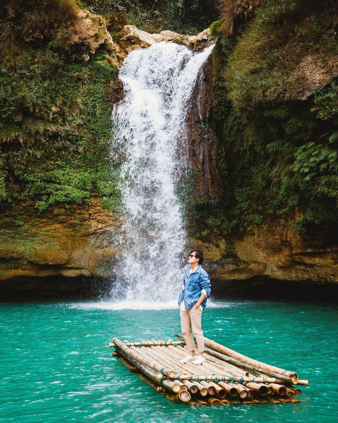 Travel blogger Mạnh Tiến Khôi thả dáng trên bè nổi giữa dòng thác xanh mướt