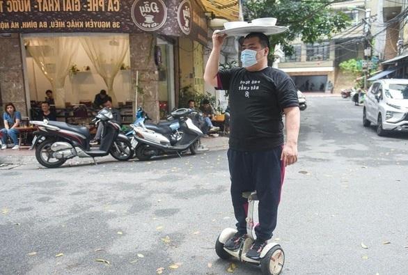 người đàn ông đi xe điện cân bằng giao phở