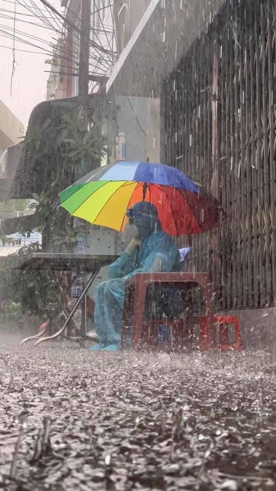 Chàng tình nguyện viên sẵn sàng cầm dù ngồi dưới mưa, nhường chỗ trú cho mọi người