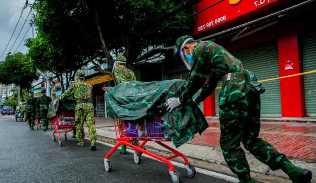 Các chiến sĩ dầm mưa mang rau củ tự trồng tặng bà con Sài Gòn