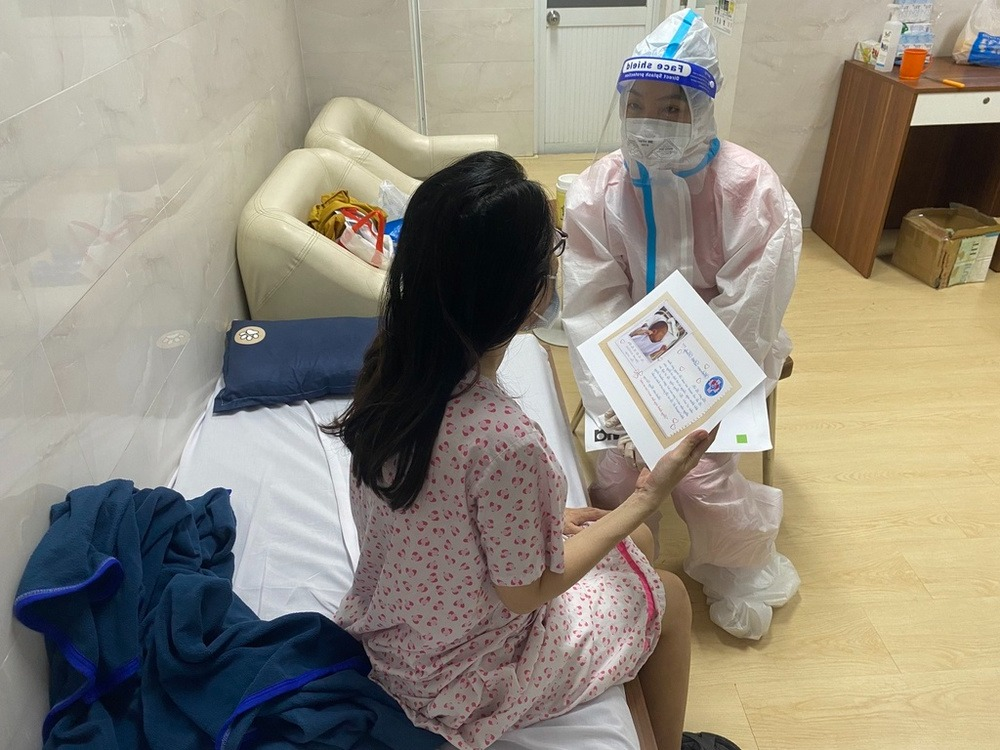 tình nguyện viên y tế chụp ảnh con gửi cho các thai phụ F0